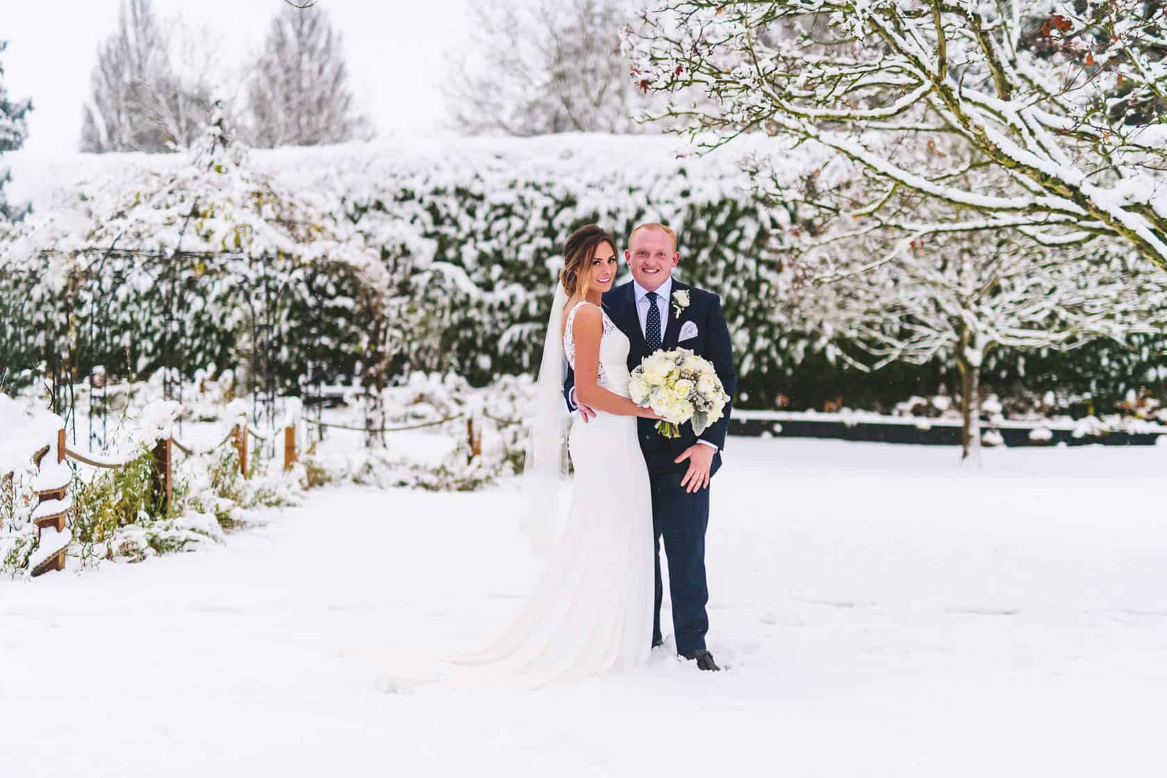 Demi and Louis standing in the Walled Garden at Gaynes Park, after it has been snowing
